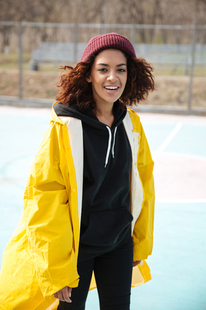 Photo of happy african young lady walking outdoors dressed in yellow raincoat. Looking at camera.