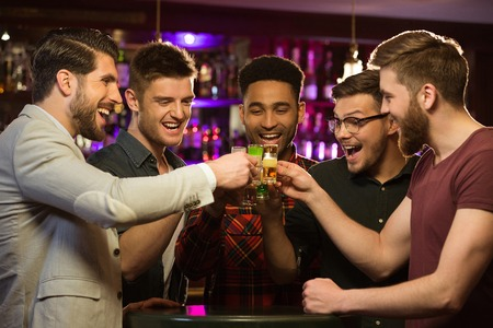 Happy male friends drinking beer and clinking glasses at bar or pub