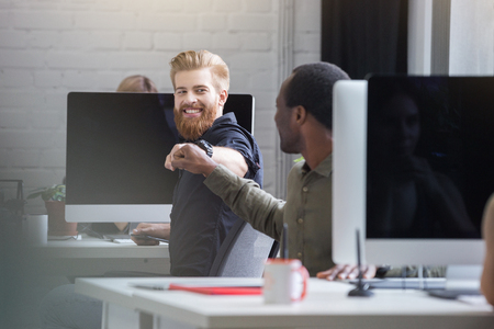 Smiling bearded man giving a fist bump to a male colleague while they are sitting at their computer desks
