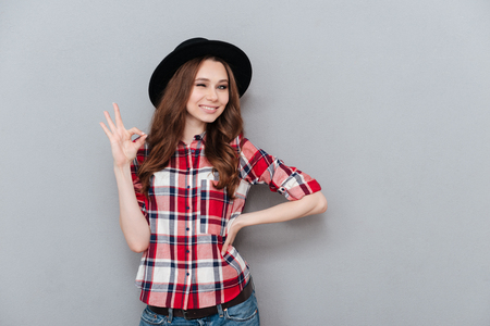 Photo pour Portrait of a young positive girl in plaid shoort showing ok gesture and winking isolated over gray background - image libre de droit