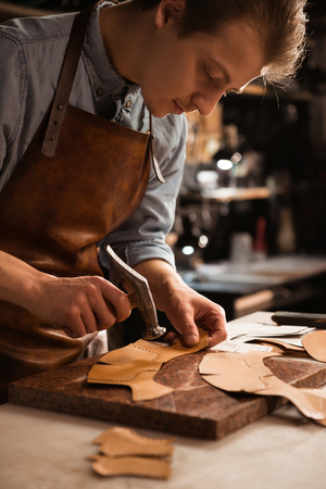 Foto per Close up of a shoemaker man working with leather using crafting tools - Immagine Royalty Free
