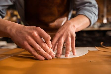 Foto de Close up of a shoemaker cutting leather in a workshop - Imagen libre de derechos