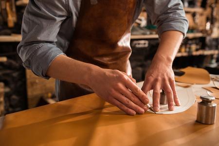 Photo pour Close up of a shoemaker cutting leather in a workshop - image libre de droit