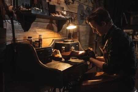 Photo pour Picture of young concentrated man shoemaker at footwear workshop. - image libre de droit