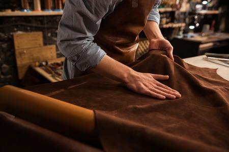 Foto de Close up of a male shoemaker working with leather textile at his workshop - Imagen libre de derechos