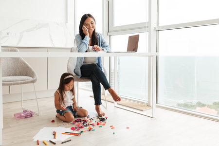 Photo for Young asian woman talking on a mobile phone and working on laptop while her little daughter playing on a floor at home - Royalty Free Image