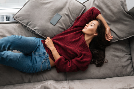 Photo pour Top view of a smiling asian woman in sweater sleeping on a couch at home with blank screen mobile phone - image libre de droit