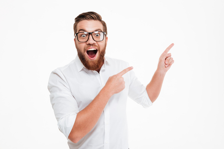 Photo pour Happy excited bearded man in eyeglasses pointing away at copy space with two fingers isolated over white background - image libre de droit