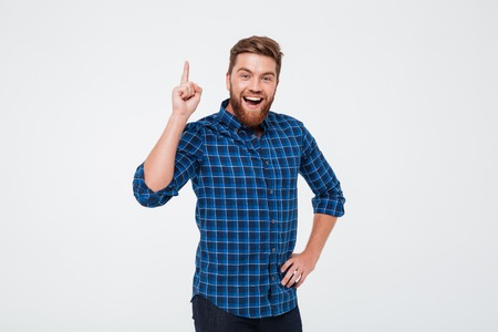 Foto de Happy cheerful bearded man pointing finger up and having an idea while standing isolated over white background - Imagen libre de derechos