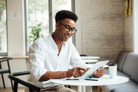 Photo for Picture of happy young african man sitting coworking with tablet computer. Looking aside. - Royalty Free Image