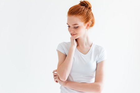 Photo pour Pretty ginger woman in t-shirt looking down over white background - image libre de droit