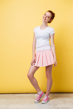 Photo for Full length image of attractive ginger girl in t-shirt and skirt looking at the camera over yellow background - Royalty Free Image