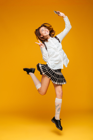 Full length portrait of an excited teenage schoolgirl in uniform with backpack taking a selfie while jumping and showing peace gesture isolated over orange backgroundの写真素材
