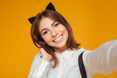 Photo for Close up portrait of a smiling teenage schoolgirl in uniform with backpack taking a selfie while standing and posing isolated over orange background - Royalty Free Image
