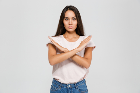 Portrait of a serious concentrated asian woman standing with crossed hands showing stop gesture isolated over white background