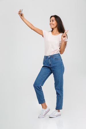 Photo pour Full length portrait of a smilin gyoung asian woman taking a selfie and showing peace gesture isolated over white background - image libre de droit