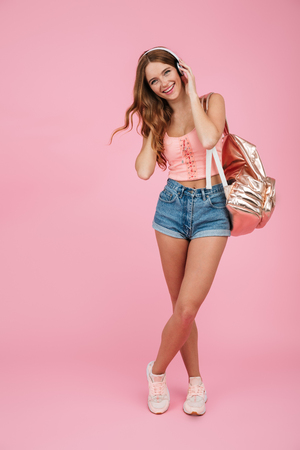 Full length portrait of young cheerful girl in summer wear with backpack, listening to music in white headphones, looking at camera, over pink background