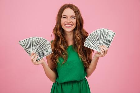 Photo pour Portrait of a smiling young woman with long hair holding bunch of money banknotes in each hand and looking at camera isolated over pink background - image libre de droit