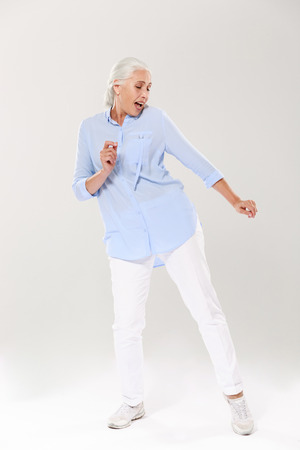 Photo pour Full-length photo of beautiful old lady, dancing and singing over white background - image libre de droit