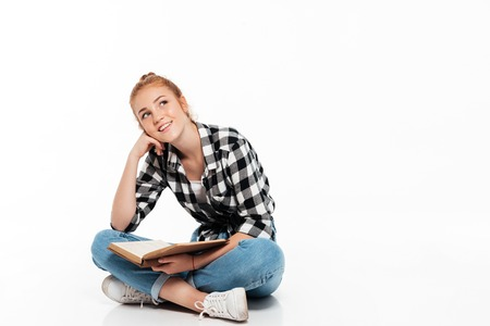 Photo pour Smiling pensive ginger woman in shirt sitting on the floor with book and looking up over white background - image libre de droit