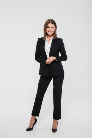 Full length portrait of confident pretty businesswoman in suit posing while standing with arms crossed and looking at camera isolated over white background
