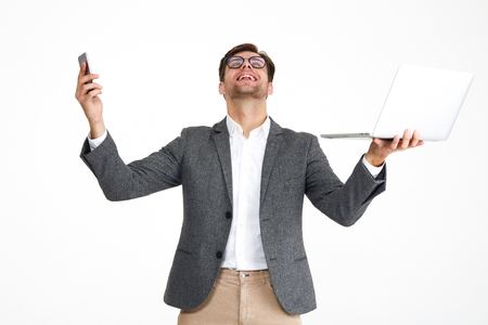 Portrait of a satisfied happy businessman in eyeglasses and a jacket holding laptop computer and mobile phone isolated over white background