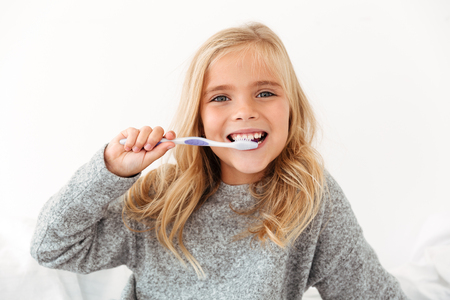 Photo pour Close-up portrait of female kid brushing her teeth, looking at camera - image libre de droit