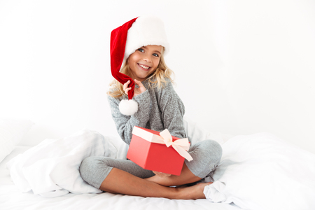 Charming little girl touching her Santa's hat holding gift box, looking at camera while sitting on bed