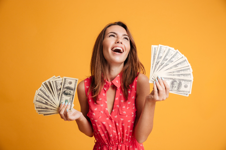 Foto de Close-up of young happy woman holding two fans of dollar bills, looking aside, isolated on yellow background - Imagen libre de derechos