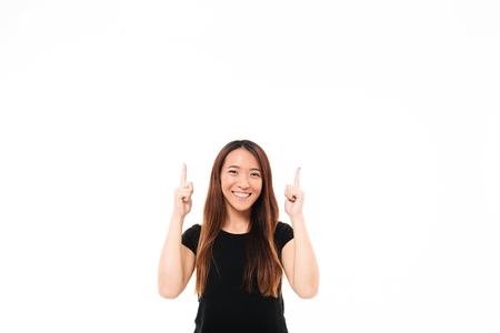 Photo pour Young cheerful asian girl in black tshirt  pointing with two fingers upward, looking at camera, isolated over white background - image libre de droit