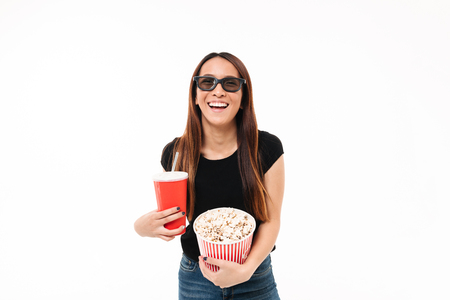 Portrait of a laughing asin girl in 3d glasses holding popcorn box and looking at camera isolated over white background