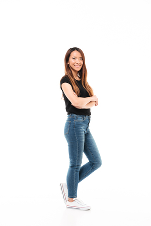 Photo pour Side view of young pretty chinese woman in black tshirt and jeans standing with crossed hands, looking at camera, isolated over white background - image libre de droit
