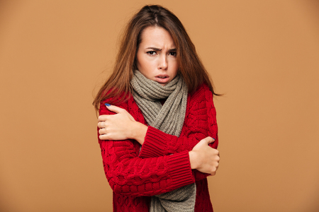 Photo pour Portrait of sad freezing brunette woman in red knitted sweater shivering while hugging herself, looking at camera, isolated on beige background - image libre de droit