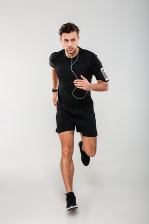 Foto de Full length portrait of a serious young man athlete in earphones listening to music while running isolated over gray background - Imagen libre de derechos