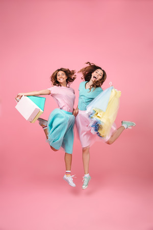 Photo pour Full length portrait of two joyful pretty girls dressed in bright colorful clothes holding shopping bags and jumping isolated over pink background - image libre de droit