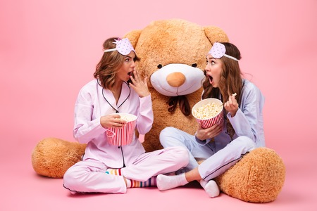 Two shocked pretty girls dressed in pajamas sitting with a big teddy bear and eating popcorn isolated over pink background