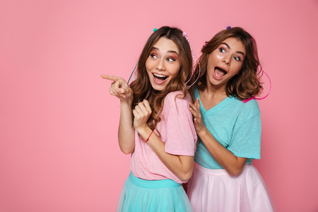 Foto de Two funny brunette woman in colorful tshirts pointing with finger, looking aside, isolated on pink background - Imagen libre de derechos