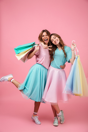 Foto de Full length portrait of two happy smiling girls dressed in bright colorful clothes holding shopping bags isolated over pink background - Imagen libre de derechos