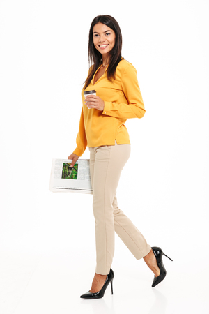 Foto de Full length portrait of a happy pretty woman holding cup of coffee and a newspaper while walking isolated over white background - Imagen libre de derechos