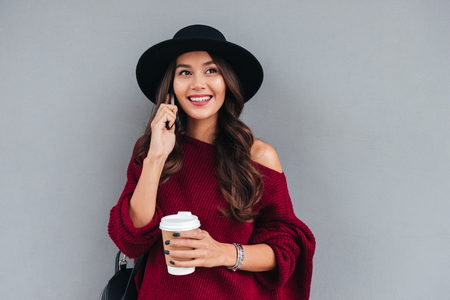 Foto de Portrait of a smiling cheerful asian girl dressed in hat and sweater holding coffee cup while talking on mobile phone on a city street - Imagen libre de derechos