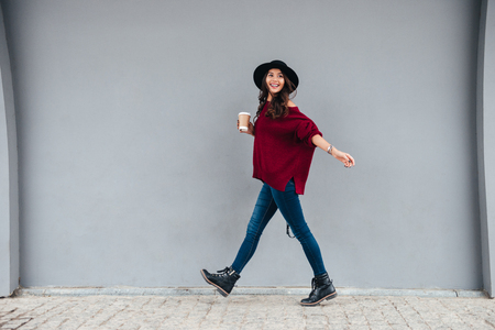Foto de Full length portrait of a smiling joyful asian girl dressed in hat and sweater holding coffee cup while walking on a city street - Imagen libre de derechos