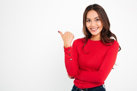 Photo for Photo of young cheerful woman standing isolated over white wall background. Looking camera pointing to copyspace. - Royalty Free Image