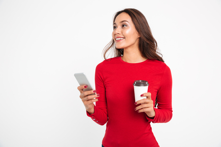Foto de Portrait of a happy smiling asian woman holding mobile phone while drinking coffee and looking up isolated over white background - Imagen libre de derechos