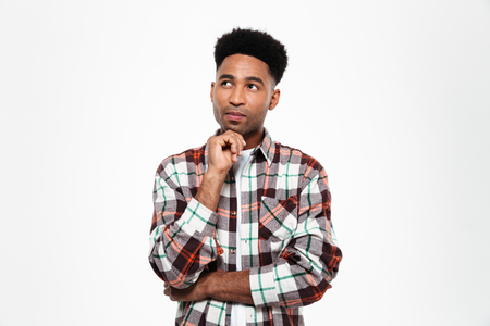 Portrait of a pensive young african man dressed in plaid shirt looking away at copy space isolated over white background