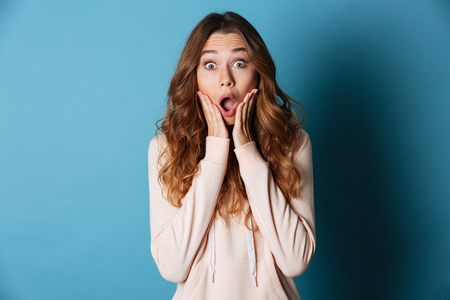 Photo pour Image of shocked young woman standing isolated over blue wall background. Looking camera. - image libre de droit