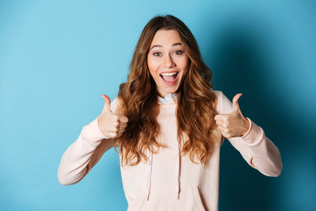 Photo pour Image of cute happy lady standing isolated over blue wall background. Looking camera showing thumbs up.. - image libre de droit