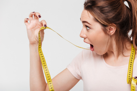 Photo for Close up portrait of a surprised young girl with open mouth looking at a measuring tape isolated over white background - Royalty Free Image