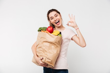 Foto de Close up portrait of a happy pretty girl holding bag with groceries and showing ok gesture isolated over white background - Imagen libre de derechos