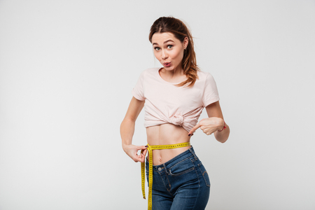 Foto de Portrait of a slim pretty woman holding measuring tape around her waist and pointing finger isolated over white background - Imagen libre de derechos