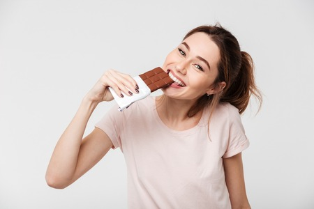 Photo pour Portrait of a smiling pretty girl biting chocolate bar and looking at camera isolated over white background - image libre de droit